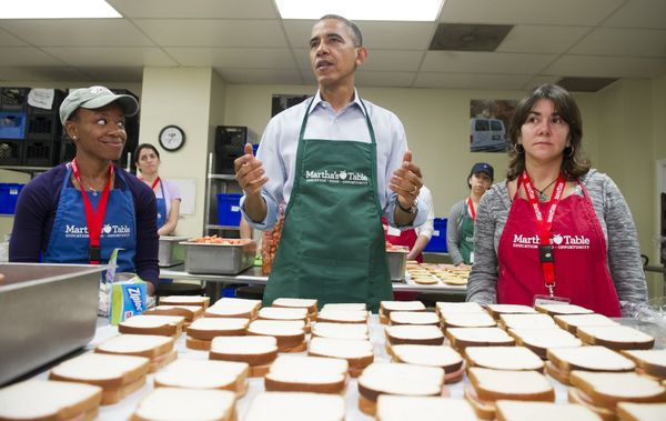 US President Barack Obama speaks to the press as he makes bologna sandwiches alongside Dolly Garcia (R), a federal employee f