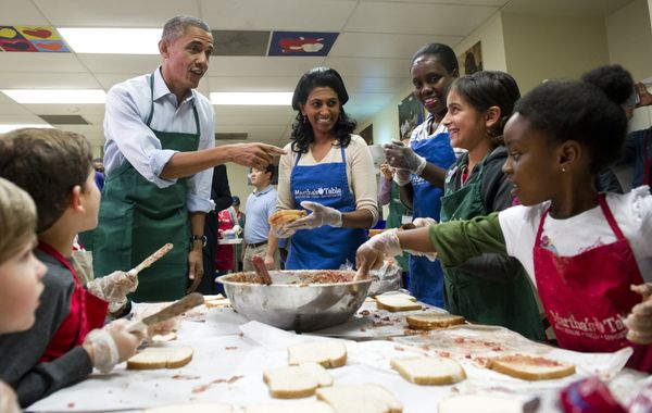 US President Barack Obama talks with children and adult volunteers that are making peanut butter and jelly sandwiches at Mart