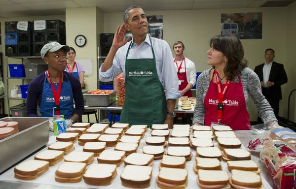 US President Barack Obama tries to hear over the noise prior to speaking to the press as he makes bologna sandwiches alongsid