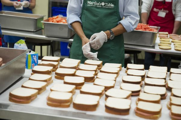 US President Barack Obama puts on protective gloves prior to making bologna sandwiches at Martha's Table in Washington, DC, O