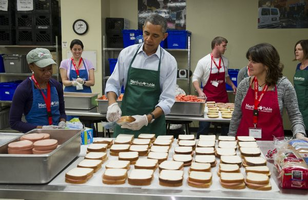US President Barack Obama makes bologna sandwiches alongside volunteers Dolly Garcia (R), a federal employee from the US Cens