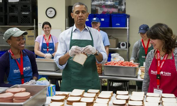 US President Barack Obama makes bologna sandwiches alongside Dolly Garcia (R), a federal employee from the US Census Bureau,