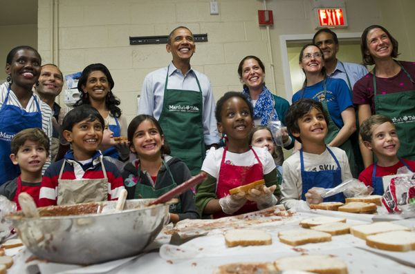 US President Barack Obama poses for photos with children and adult volunteers that are making peanut butter and jelly sandwic