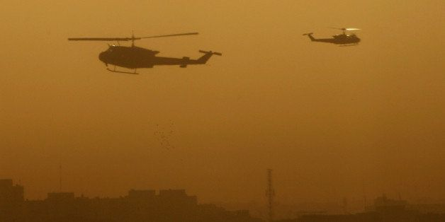 Military helicopters fly over the Green Zone area in Baghdad following a loud explosion early on October 18, 2010. Violence i
