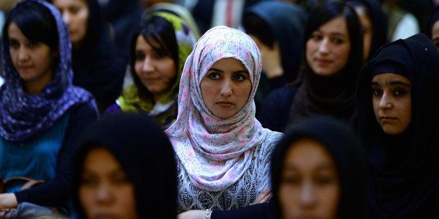 Afghan women listen to a speaker address a political gathering at a wedding hall in Kabul on September 26, 2013.   Member of