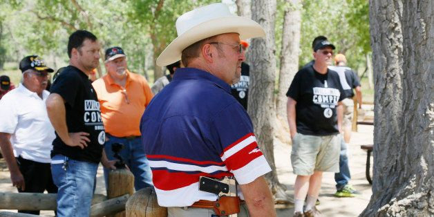 James Rybolt, carrying a .45 Colt pistol, listens at a rally sponsored by Rocky Mountain Gun Owners, marking the one-year ann
