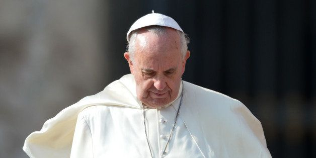 The wind lifts the skullcap of Pope Francis as he leaves after his general audience at St Peter's square on October 30, 2013
