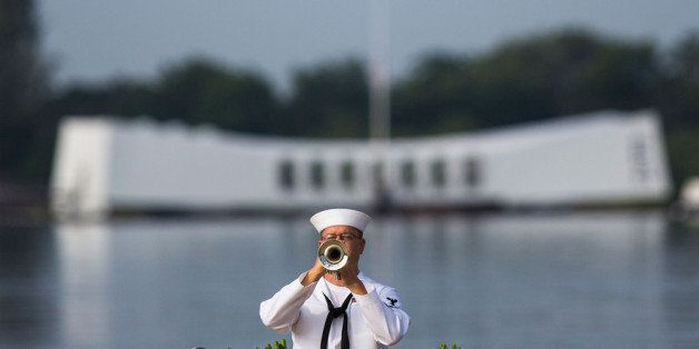 PEARL HARBOR, HAWAII - DECEMBER 7:   A U.S. Navy musician plays echo 'Taps' in front of the U.S.S. Arizona Memorial during th