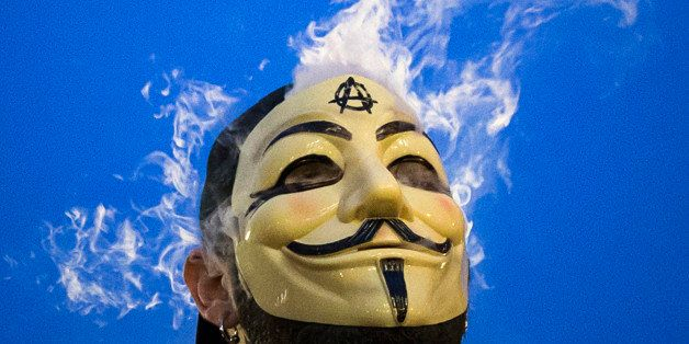 Vapor passes through a Guy Fawkes mask as a man smokes while joining supporters of the Anonymous movement who were taking par