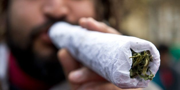 A man holds a giant joint during a march for the legalization of cannabis in Santiago, on May 18, 2013, as part of the 2013 G