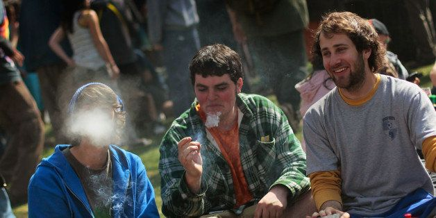 BOULDER, CO - APRIL 20:  Young men smoke a marijuana cigarette during a 'smoke out' with thousands of others April 20, 2010 a
