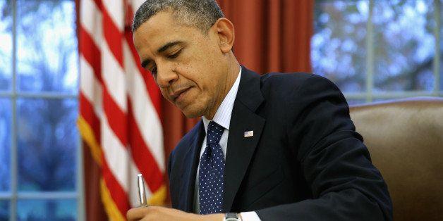 WASHINGTON, DC - NOVEMBER 27:  U.S. President Barack Obama signs three bills into law on the Resolute Desk inside the Oval Of