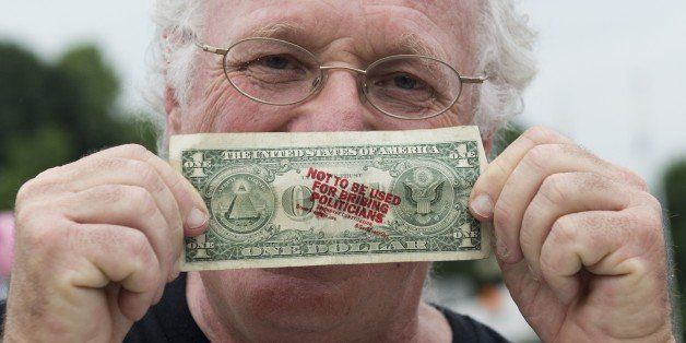 Ben Cohen, co-founder of Ben & Jerry's Ice Cream, holds up a one-dollar bill he stamped with the words 'Not to be used for br