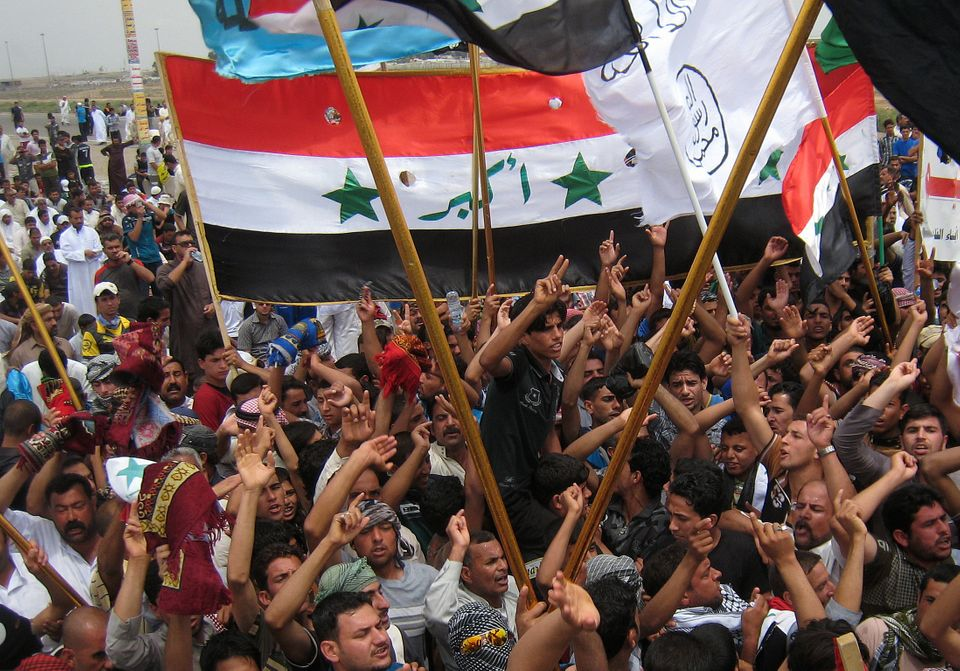 Iraqis chant anti-government slogans as others wave representations of older national flags at an anti-government rally in Fa