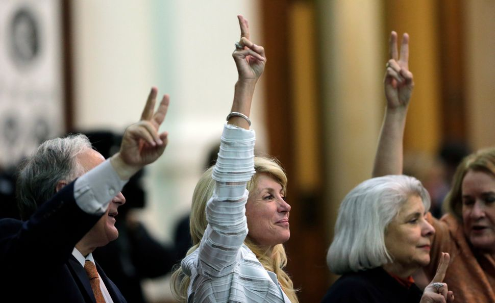 """Sen. Wendy Davis (D-Ft. Worth), center, holds up two fingers to signal a """"No"""" vote as an 11-hour session where she tried to f"""