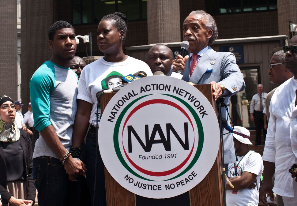 Rev. Al Sharpton speaks as Trayvon Martin's mother Sybrina Fulton and Martin's brother Jahvaris Fulton (left) attend a rally