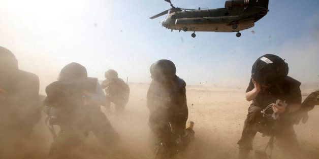 HELMAND, AFGHANISTAN - DECEMBER 16: Members of the media try to protect themselves from dust blown up by a British forces tra