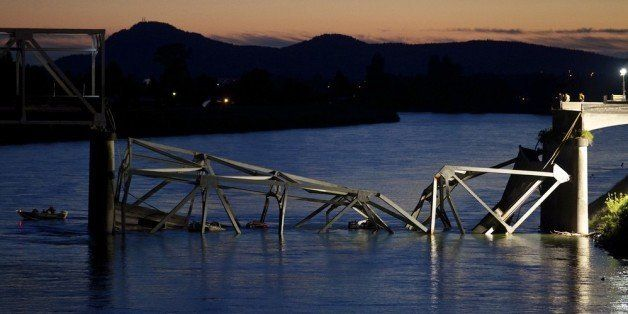 MT. VERNON, WASHINGTON  - MAY 23: A boat cruises past the scene of a bridge collapse on Interstate 5 on May 23, 2013 near Mt.