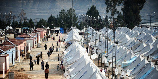 Syrian refugees walk among tents at Karkamis' refugee camp on January 16, 2014 near the town of Gaziantep, south of Turkey. T