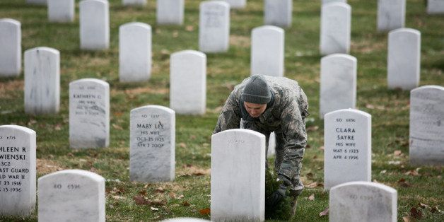 ARLINGTON, VA - DECEMBER 14:  Army Tech Sgt. Danielle Williams, stationed at Fort Belvoir, lays a wreath at the foot of a hea