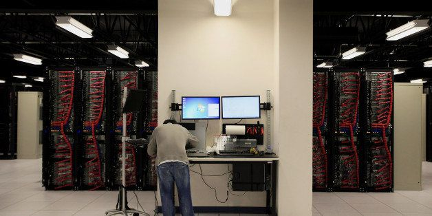A server build technician stands at a work bench while monitoring a clients data and performing maintenance inside pod two of