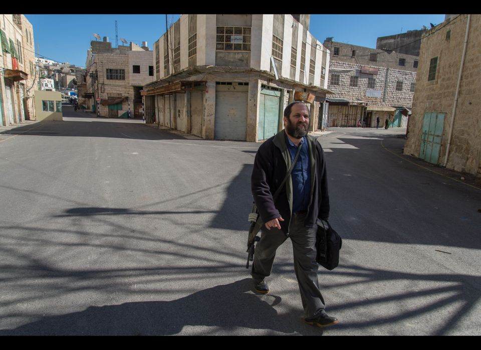 Armed Israeli settler strolls across checkpoint in Hebron, West Bank. (Photo: Thomas Dallal)