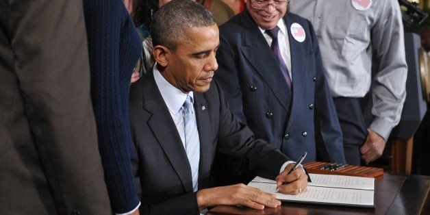 US President Barack Obama signs an executive order raising the federal minimum wage to $10.10 on new federal contracts in the