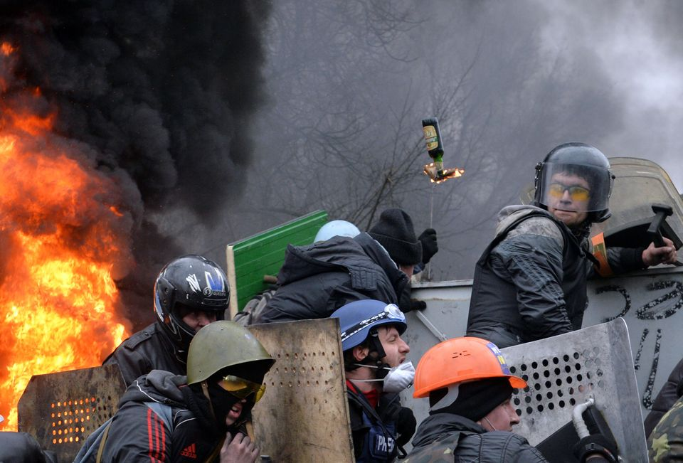 Anti-government protesters take cover while under fire from police snipers during clashes with riot police in central Kiev on