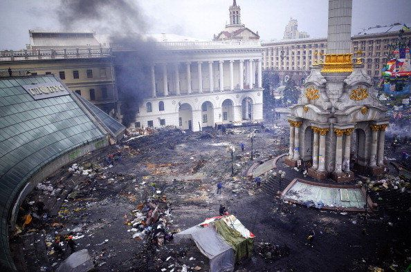 <br>Protestors inspect damage caused by recent anti-government protests on Independence Square following recent clashes in Ki
