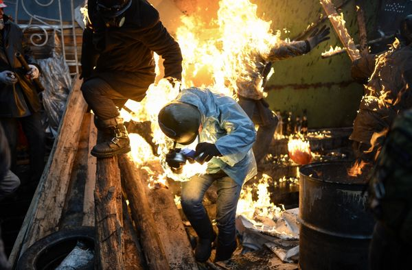 Protesters catch fire as they stand behind burning barricades during clashes with police on Feb. 20, 2014, in Kiev. Ukraine's