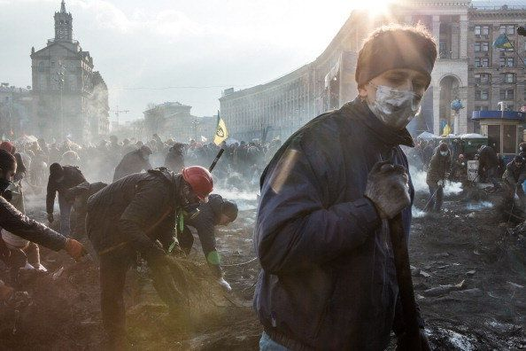 <br>Anti-government protesters clear ashes and debris from a newly occupied portion of Independence Square on Feb. 20, 2014,