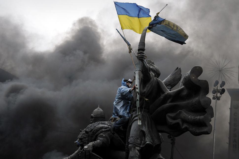 <br>An anti-government protester sits on the Founders of Kiev monument during clashes with riot police in central Kiev on Feb