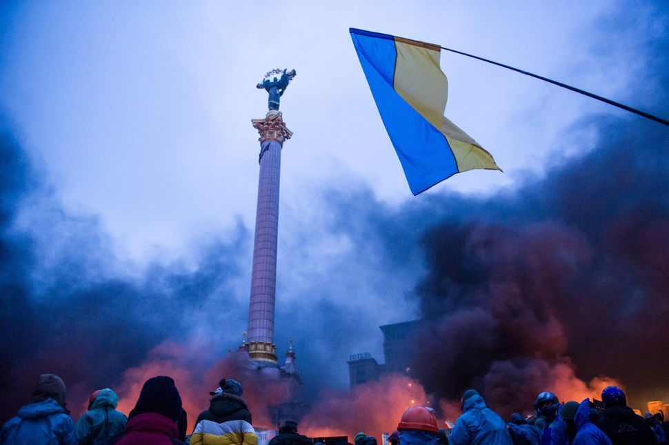 <br>Anti-government protesters stand behind a 'wall of smoke' during clashes with police in the center of Kiev on Feb. 20, 20