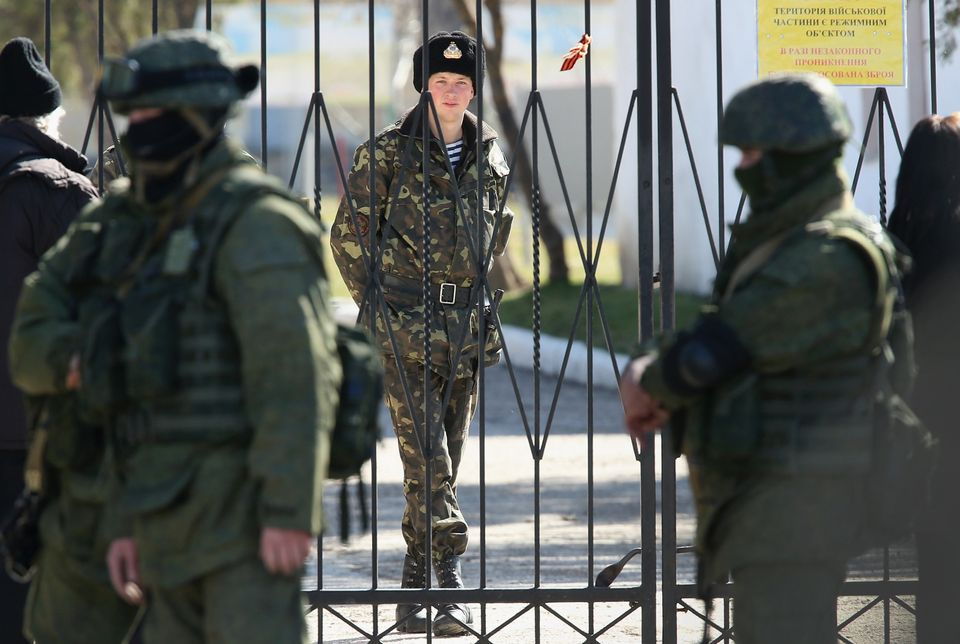 A Ukrainian soldier stands inside the gate of a Ukrainian military base as unidentified heavily-armed soldiers stand outside