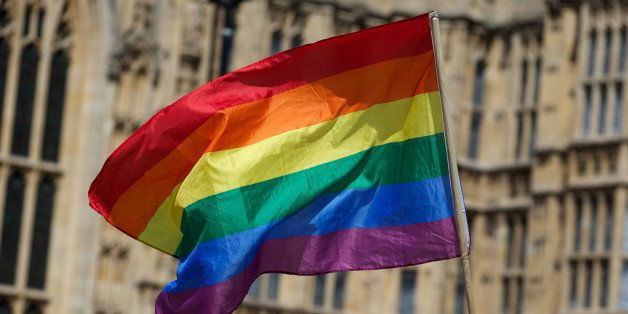 A gay campaigner waves the rainbow flag during a rally outside the Houses of Parliament as the Marriage (Same Sex Couples) Bi