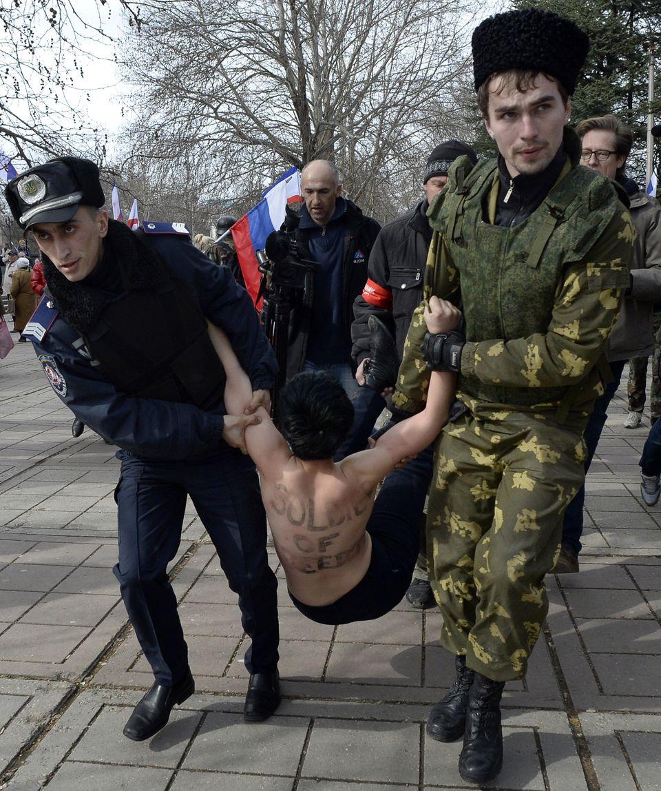 A Ukrainian police officer (L) and a pro-Russian volunteer (R) detain a topless activist of the Ukrainian women movement Feme