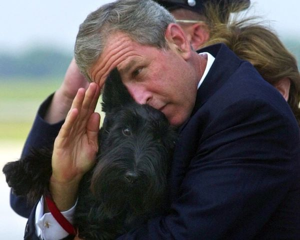 FILE - In this June 25, 2001 file photo, President Bush does his best to salute while holding his dog Barney as they get off