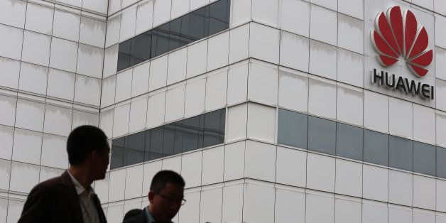 People walk by a building on the Huawei campus in the Chinese city of Shenzhen on April 7, 2013. Chinese tech giant Huawei sa