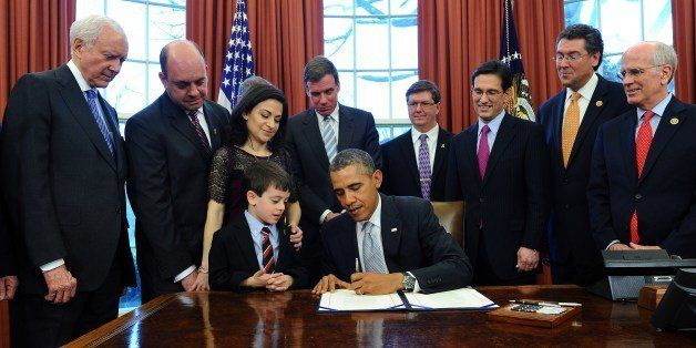 US President Barack Obama is watched by Gabriella Miller's family (L) and lawmakers as he signs the Gabriella Miller Kids Fir