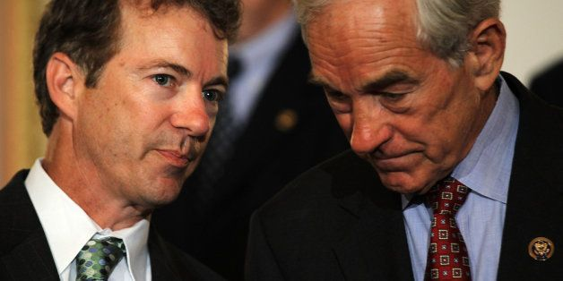 WASHINGTON - JUNE 22:  U.S. Sen. Rand Paul (R-KY) (L) talks to his father Rep. Ron Paul (R-TX) (R) during a news conference J