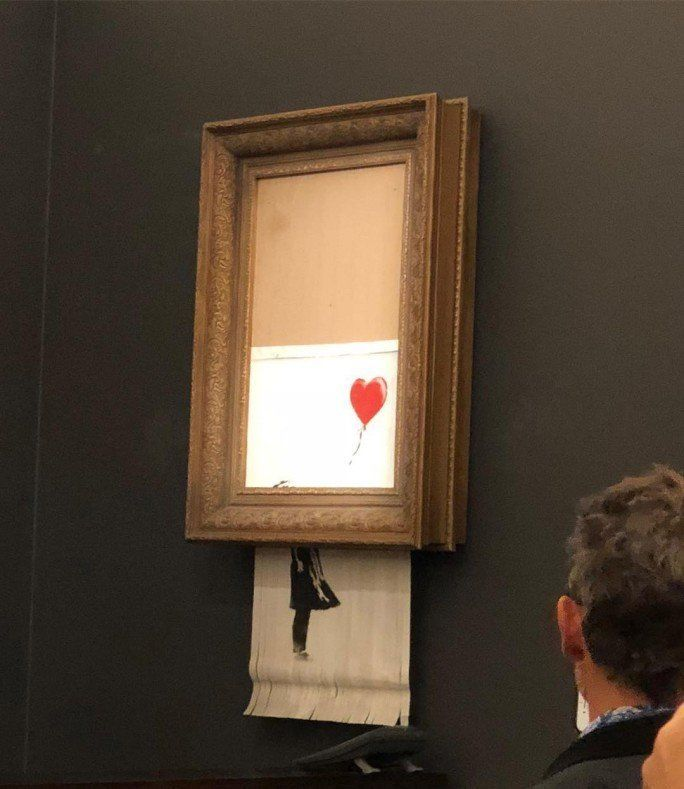 The iconic painting passes through the shredder as stunned onlookers