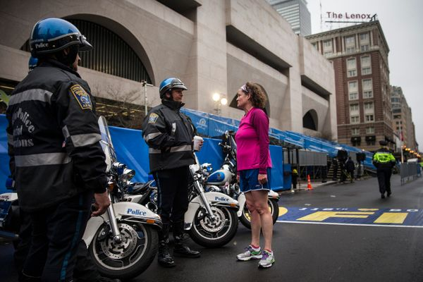 Runner speaks to Boston police officers at the finish line of the Boston Marathon on the morning of the anniversary.