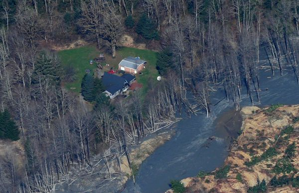 An intact house sits at left at the edge of the massive mudslide that killed at least eight people and left dozens missing is