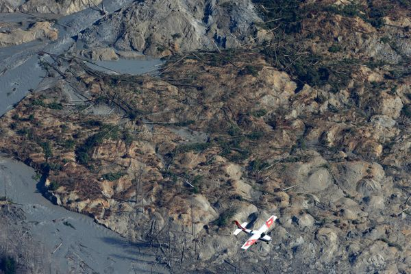 A Civil Air Patrol plane flies over the massive mudslide that killed at least eight people and left dozens missing as shown i