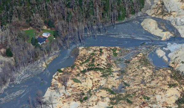 An intact house sits at left at the edge of the massive mudslide