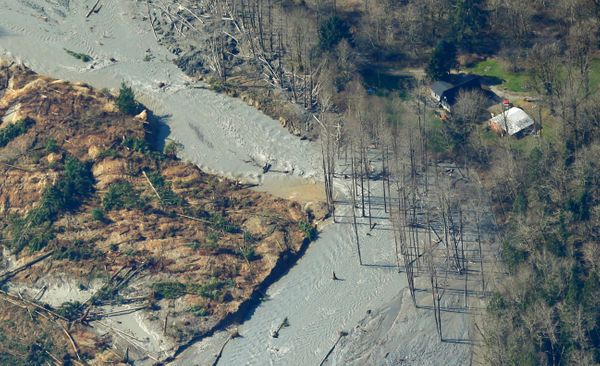 An intact house is shown at right near where water from the Stillaguamish River is flowing around the edge of the massive mud