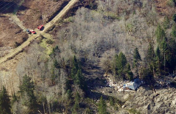 Emergency vehicles are shown parked on a road leading to the remains of a house destroyed by the massive mudslide