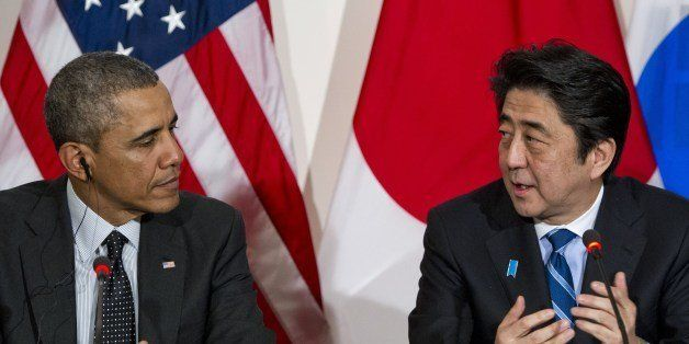 US President Barack Obama listens to Japanese Prime Minister Shinzo Abe (R) during a trilateral meeting with the South Korean
