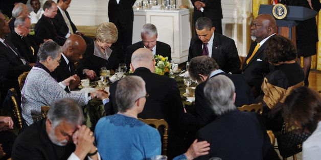US President Barack Obama bows his head in prayer during an Easter prayer breakfast April 19, 2011 in the East Room of the Wh