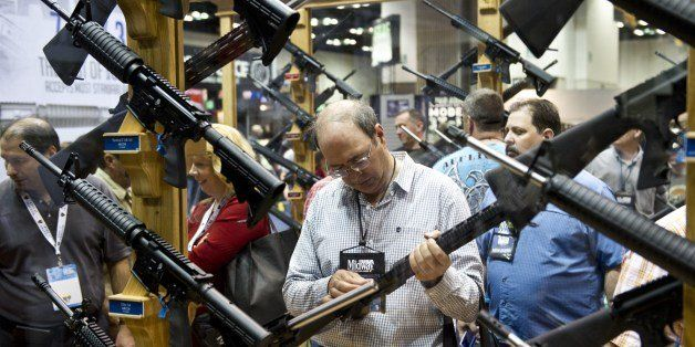 A convention goer examines weapons in the exhibit hall at the143rd NRA Annual Meetings and Exhibits at the Indiana Convention
